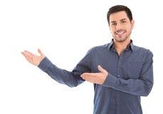 Изолированный усмехаясь человек представляя с его руками стоковое фото