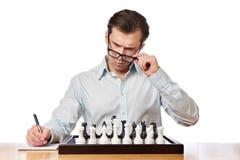 Изолированный человек в стеклах играя шахмат Стоковое фото RF