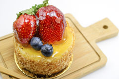 Изолированный чизкейк ягод на деревянной разделочной доске, ягодах сладостных Стоковое фото RF