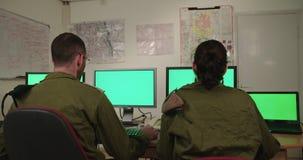 Израильские солдаты в военном командовании и диспетчерском пункте смотря экраны