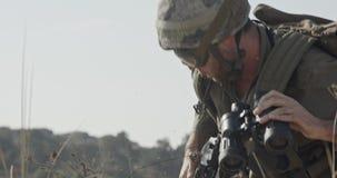 Израильский солдат вползая от крышки и смотря через бинокли сток-видео