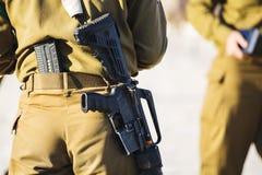 Израильский солдат с оружием, съемка девушки от задней части Стоковое Фото