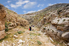 ИЗРАИЛЬ, ПУСТЫНЯ НЕГЕВ - 7-ОЕ АПРЕЛЯ 2016: люди идут через скалистую пустыню ИЗРАИЛЬ, ПУСТЫНЯ НЕГЕВ Стоковое Изображение