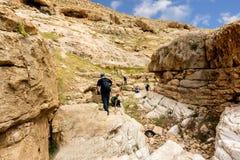 ИЗРАИЛЬ, ПУСТЫНЯ НЕГЕВ - 7-ОЕ АПРЕЛЯ 2016: люди идут через скалистую пустыню ИЗРАИЛЬ, ПУСТЫНЯ НЕГЕВ Стоковые Изображения