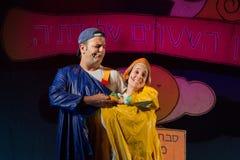 Израиль, пиво-Sheva - театр детей актеров на этапе в голубом и желтом плаще 2015 стоковые изображения