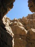 Изрезанные геологохимические слои утеса обрамляют небо над узким следом каньона шлица Стоковое Изображение