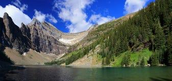 Изрезанные горные пики окружая озеро Agnes над национальный парк Lake Louise, Banff, Альберта стоковая фотография rf
