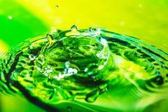 Изумительная абстрактная съемка выплеска падения воды на зеленых лист в воде Зеленая и желтая предпосылка Макрос снятый с селекти Стоковая Фотография RF