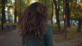 Изумительная девушка с курчавым стилем причёсок в прогулке пальто в переулке и усмехаться осени видеоматериал