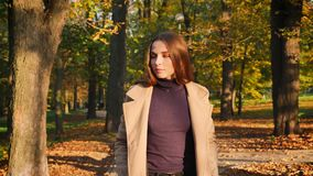 Изумительная кавказская женщина в парке идя холодок к камере и смотреть ослабленный взгляд парка счастливый и, наслаждающся паден акции видеоматериалы