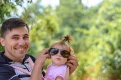 Изумительная маленькая девочка играет с солнечными очками с ее отцом стоковые фото
