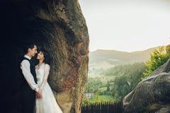 Изумительная пара свадьбы обнимает один другого в горах Стоковое Изображение RF