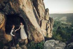 Изумительная пара свадьбы обнимает один другого в горах Стоковые Изображения