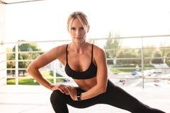 Изумительная сильная женщина спорт детенышей делает спорт протягивая тренировки Стоковые Фото
