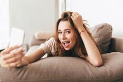 Изумительная эмоциональная милая дама делает selfie телефоном стоковое фото rf