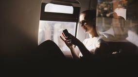 Изумительное отражение сняло счастливой европейской девушки усмехаясь, используя smartphone app сидя на современном moving сидень видеоматериал