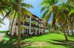 Изумительный взгляд колониальных земель гостиницы, красивых приглашая ретро стильных зданий в тропическом саде на голубом небе Стоковое Изображение RF
