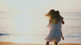 Изумительный взгляд семьи счастливой красивой матери и маленькой дочери закручивая совместно ослаблять на изумляя пляж моря заход видеоматериал
