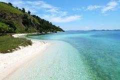 Изумительный ландшафт seashore с белым песком, волнами разбивая, ясное tosca покрасил воду и славные зеленые холмы Стоковая Фотография RF