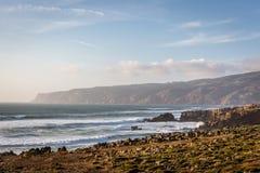 Изумительный сценарий ландшафта на пляже Guincho в Cascais, Португалии Цвета захода солнца, горы, большие волны стоковое изображение rf