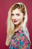 Изумительная блондинка в красочной рубашке смотря камеру и усмехаясь на розовой предпосылке Милая девушка представляя в студии Стоковые Изображения