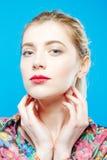 Изумительная блондинка при чувственные губы и совершенная кожа нося красочную рубашку на голубой предпосылке в студии женщина вни Стоковое Фото