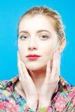 Изумительная девушка при чувственные губы и совершенная кожа нося красочную рубашку на голубой предпосылке в студии женщина внима Стоковое Изображение