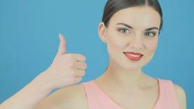 Изумительная женщина показывает большие пальцы руки вверх на голубой предпосылке в студии Красивое брюнет жестикулирует смотрящ к акции видеоматериалы