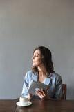 Изумительная женщина сидя внутри помещения используя планшет Стоковые Изображения RF