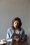 Изумительная женщина сидя внутри помещения используя планшет Стоковое Фото