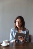 Изумительная женщина сидя внутри помещения используя планшет Стоковые Изображения