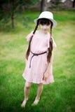 Изумительная маленькая девочка в розовом платье и белой шляпе стоковые фотографии rf