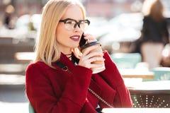 Изумительная молодая кавказская женщина говоря кофе телефона выпивая Стоковое Фото