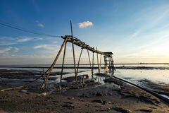 Изумительная тропическая предпосылка захода солнца, деревянная башня водяной помпы на тинном пляже Стоковое фото RF