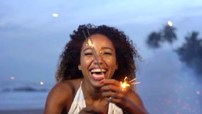 Изумительное торжество при женщина держа танцы бенгальского огня и скача с фейерверками на заднем плане на пляж в замедленном дви сток-видео