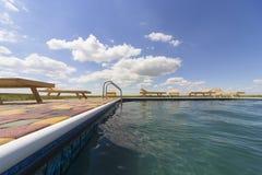 Изумительные взгляды над бассейном с деревянными loungers солнца Стоковое фото RF