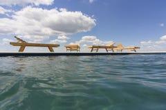 Изумительные взгляды над бассейном с деревянными loungers солнца Стоковое Изображение