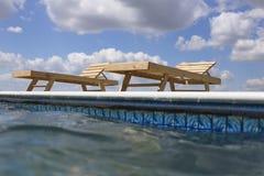 Изумительные взгляды над бассейном с деревянными loungers солнца Стоковая Фотография RF