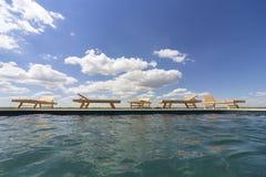 Изумительные взгляды над бассейном с деревянными loungers солнца Стоковое Фото