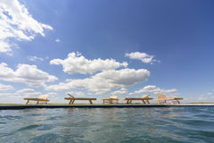 Изумительные взгляды над бассейном с деревянными loungers солнца Стоковые Фото