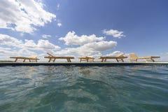 Изумительные взгляды над бассейном с деревянными loungers солнца Стоковые Изображения