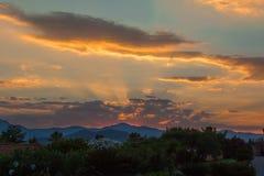 Изумительный заход солнца среди холмов и облаков Стоковые Фотографии RF