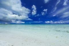 Изумительный сногсшибательный взгляд холодного синего драматического sky& x27; s с белыми пушистыми облаками над спокойной бирюзо Стоковые Фотографии RF