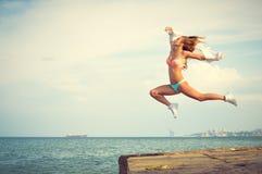Изумительный танцор в swimwear скача вверх по максимуму дальше стоковые фотографии rf