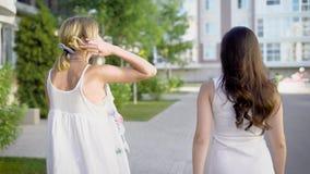 2 изумительных женщины нося белые платья идут вниз с переулка и peacfully говорят о что-то акции видеоматериалы