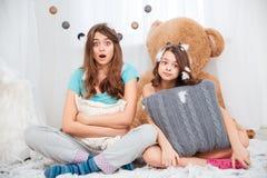 2 изумили симпатичные сестер сидя и обнимая подушка Стоковая Фотография RF