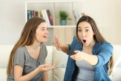 Изумленная девушка прерывая ее друга для того чтобы посмотреть ТВ Стоковое Изображение RF