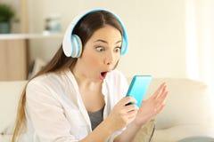 Изумленная девушка слушая к музыке находя онлайн предложение Стоковое Изображение