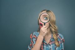 Изумленная девушка смотрит через лупу и интересовать Она исследователь Изолировано на голубой предпосылке Стоковые Изображения RF
