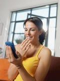изумленная женщина удерживания мобильного телефона стоковое изображение rf